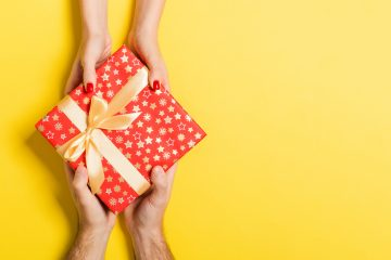 Top view of a man and a woman giving and receiving gift for a holiday on colorful background. Love and relationship concept with copy space